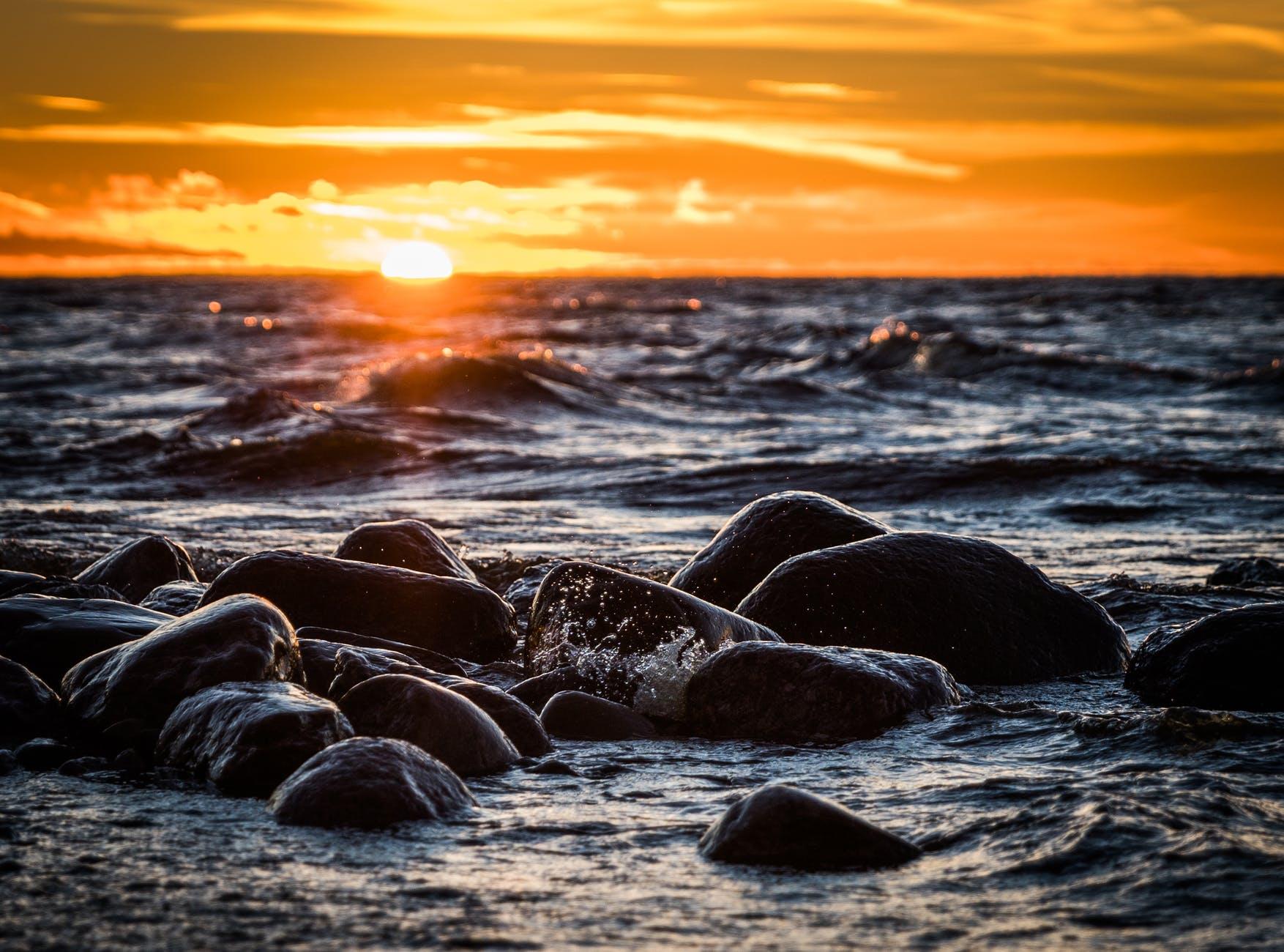 stones on beach during sunset